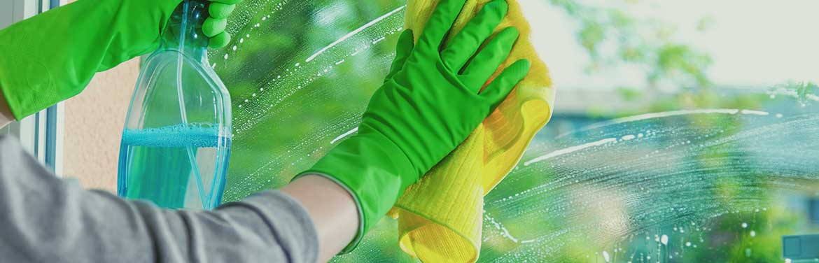person with green rubber gloves cleaning a window